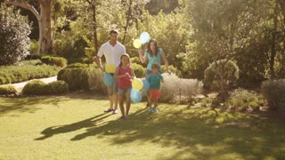 Family in park running with balloons.