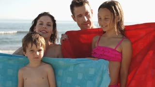 Family on beach, parents wrapping children in towels.