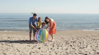 Family on beach rolling beach ball towards camera.