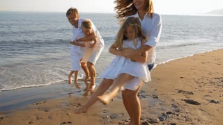 family on beach twirling around