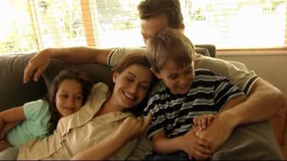 Family on sofa cuddling and tickling