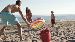 Family playing football with beach ball on beach.