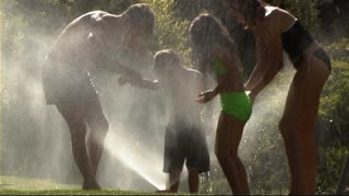 Family playing in water spray