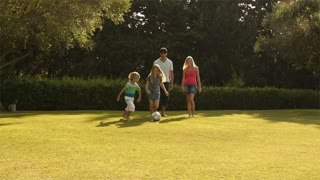 Family playing soccer in garden.