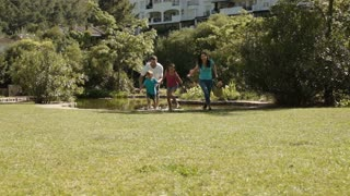 Family running to camera in a park.