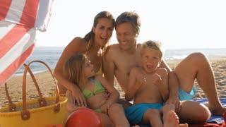 family sitting together under beach umbrella