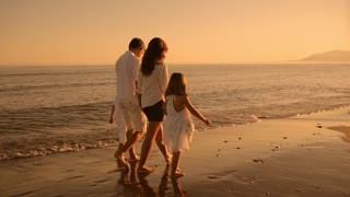 family standing on beach in sunset