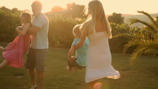 family twirling in sunset