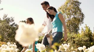 Family walking in park with white flowers in foreground.