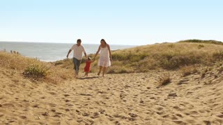 Family walking on sand dunes to camera.