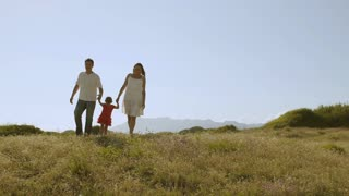 Family walking through meadow to camera.