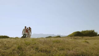 Family walking through meadow to camera.