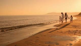 family walking towards camera on beach in sunset