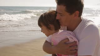Father and daughter hugging at the beach.