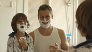 Father and son with shaving cream on their faces.