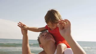 Father giving his daughter a shoulder ride at beach.