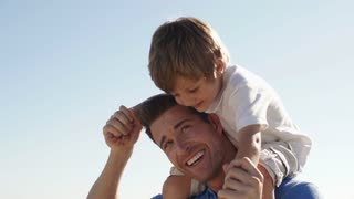 Father playing with son on shoulders at beach.
