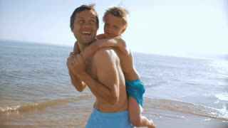 father twirling with son on back on beach