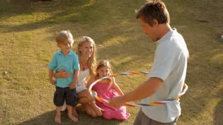 father with hula hoop being watched by family