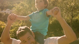 Father with son on shoulders in park.