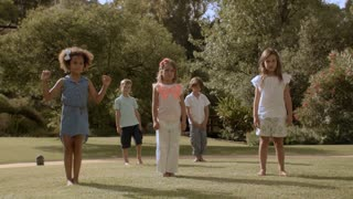 Five children doing star jumps in park