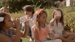 Five children drinking bottles of water in park