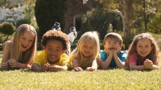 Five children lying on grass in park looking at camera.