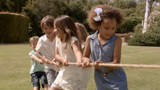 Five children pulling rope having tug of war in park