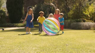 Five children pushing beach ball towards camera in park.