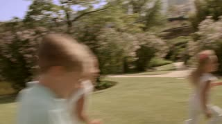 Five children running around camera in park