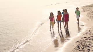 Five children running on beach.