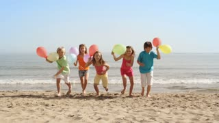 Five children running towards camera on beach holding balloons.
