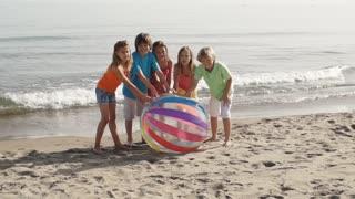 Five children running towards camera on beach pushing beach ball.