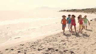 Five children running towards camera on beach.