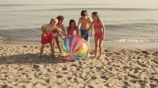 Five children running towards camera pushing beach ball on beach.