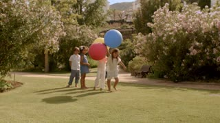 Five children running with balloons in park