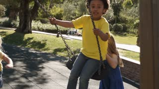 Four children playing on swings in park.