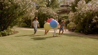 Four children running with balloons in park