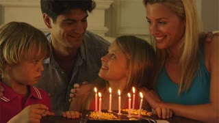 Girl blowing out  candles on birthday cake.