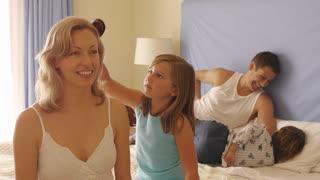 Girl brushing her mother's hair in bedroom.
