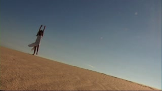 Girl doing cartwheels in the sand dunes