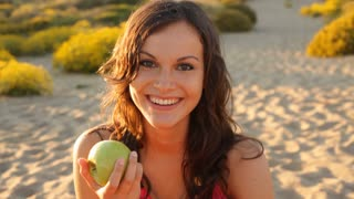 Girl eating apple on beach