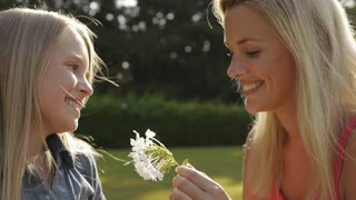 Girl giving her mother a flower in garden.