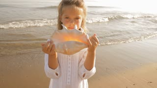 girl with large shell on beach
