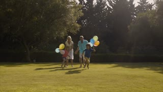 Grandchildren and grandparents running to camera in garden holding balloons.