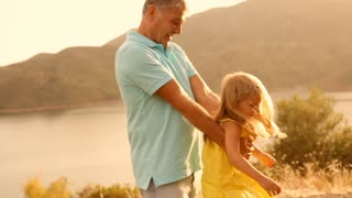 Grandfather and grandchild playing in sunset