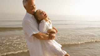 grandfather and granddaughter twirling on beach