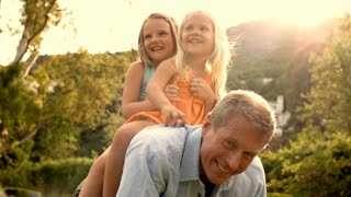 Grandfather carrying two granddaughters on his back in park.