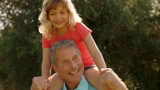 Grandfather playing with granddaughter on his shoulders in garden.