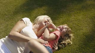 Grandmother and granddaughter playing on grass in garden.